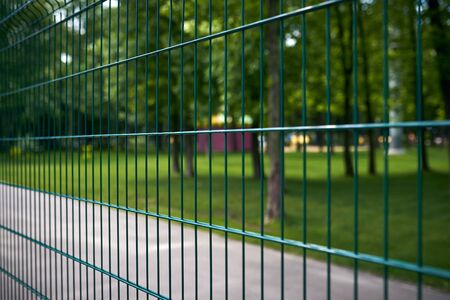 fence at thw public park at summer day close up