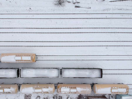 Aerial view of a cargo trains in witer. Freight trains covered with snow on the railway station. Heavy industry. No people.