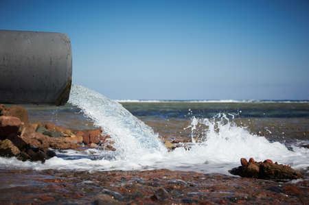 clear water flows from a pipe into the sea.