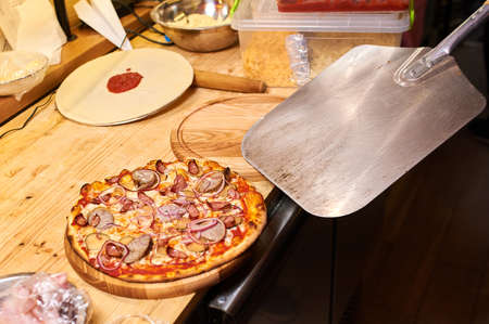 Freshly baked pizza with bacon, onion and pepper lie on a shovel among the ingredients in flour on a wooden table