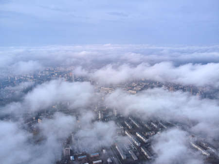 Above the clouds on a sunny day, view from a drone. big city houses are visible through the clouds.