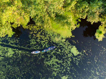 Aerial view over the river which is on the green forest. drone photo