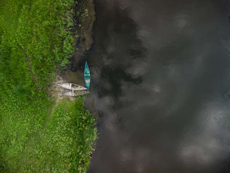 aerial top down view of old wooden boats near river bank on summer day