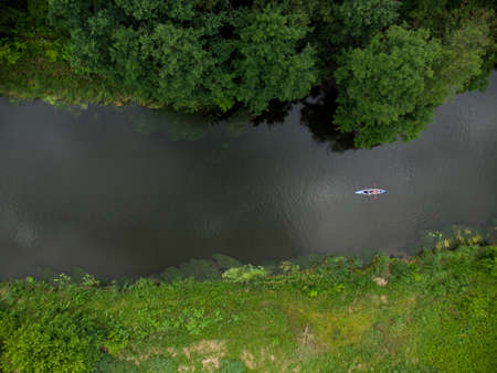 aerial view of a large group of kayaks traveling on a forest river on a summer day