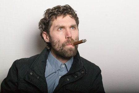 smoking a cigar: bearded man sitting on a chair and smoking a cigar