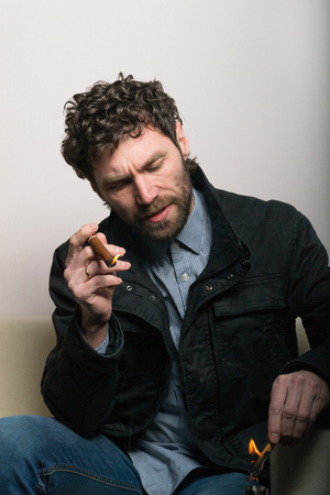 hombre fumando puro: bearded man sitting on a chair and smoking a cigar