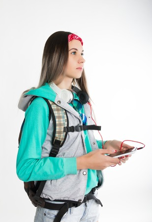 coed: Young brunette female student standing, looks into the distance and holding your smartphone. Beautiful young backpacker