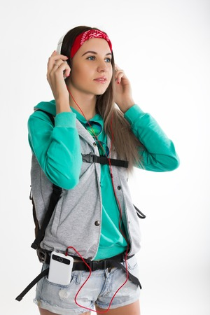 coed: Young brunette female student standing and listening to music from your device. Beautiful young backpacker