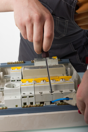 electrical appliance: electrical appliance repairs. electrician fixing cable in domestic electrical box