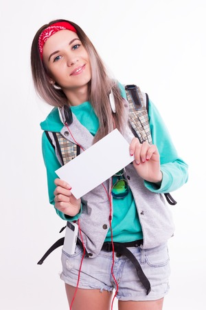 coed: Young brunette female student standing and listening to music from your device. Beautiful young backpacker. Young female student holding a white sheet