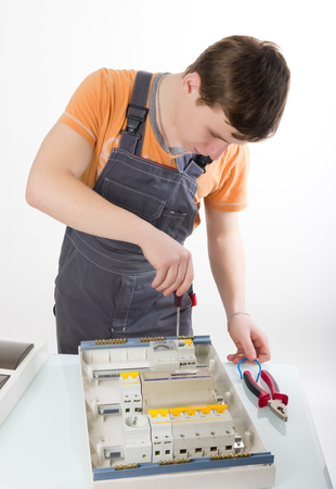 electrical appliance: electrical appliance repairs. electrician fixing cable in domestic electrical plastic box