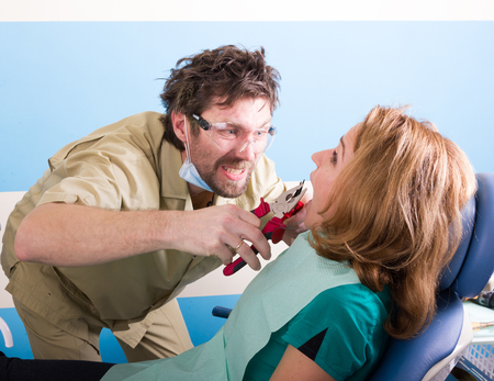 unfortunate: Crazy dentist treats teeth of the unfortunate patient. The patient is terrified. MAD dentist Stock Photo