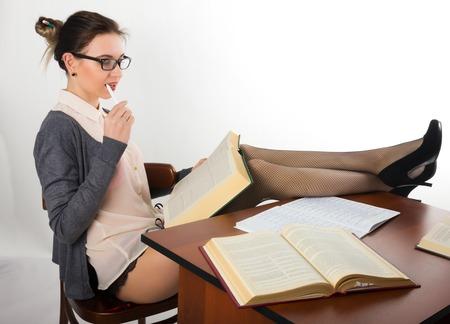 material de vidrio: joven y bella profesora atractiva que se sienta en la mesa y lee el libro Foto de archivo