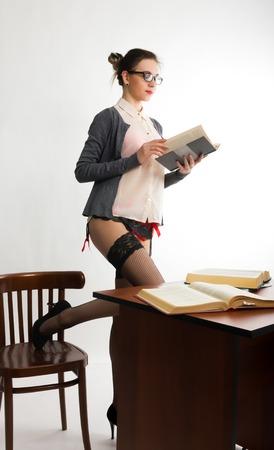 jeune sexy belle enseignante debout à côté de la table et lit le livre