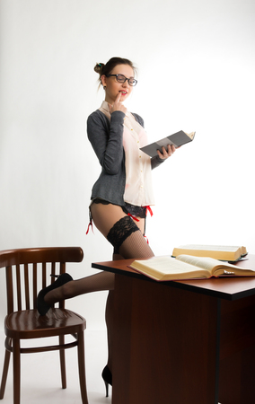 Sexy young beautiful female teacher standing next to the table  and reads the book