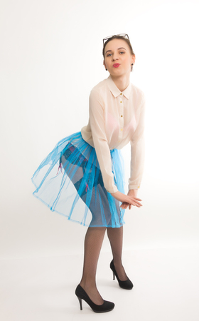 garters: Full length portrait of a beautiful sexy slim model in a blue skirt and white blouse transparent, in stockings and garters Stock Photo