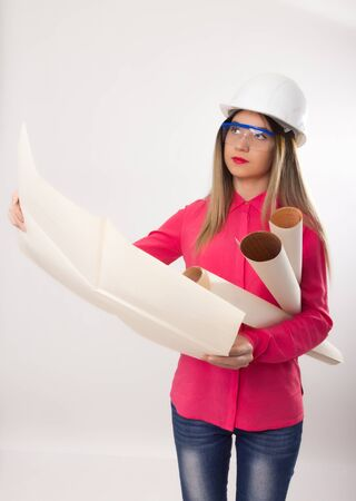 an operative: beautiful woman civil engineer holding blueprints, young female architect Stock Photo