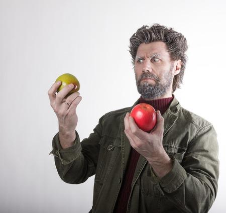 Mr. IceMan, 수염을 가진 웃는 남자, 수염을 뒤덮은 수염, 사과를 든 남자, 그는 그들을 응시합니다. 패션 남자 니트 스웨터와 자 켓입니다.