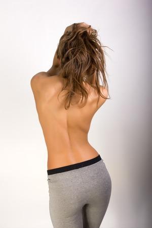 Slim sexy girl in a gray leggings, she turned her back bare