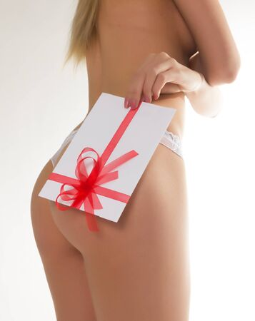 giftwrapped: beautiful girl in lacy shorts with an envelope tied with ribbon