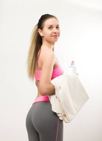perspire: Young athletic girl finished training, holding bath towel Stock Photo