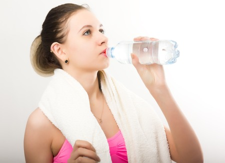 freshening: Young athletic girl finished training, holding bath towel, drinks water from a bottle