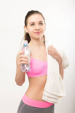 perspire: Young athletic girl finished training, holding bath towel, drinks water from a bottle