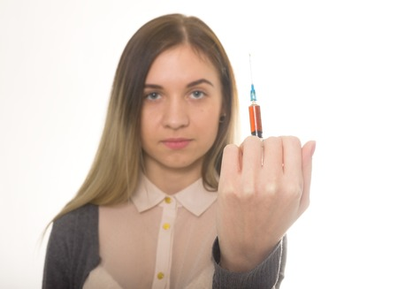 drug use: The social problem. Young sad woman holding syringe to drug use Stock Photo