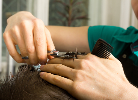 hairdressing scissors: hairdresser  cuts   hair  with scissors on crown of handsome satisfied  client in  professional  hairdressing salon Stock Photo