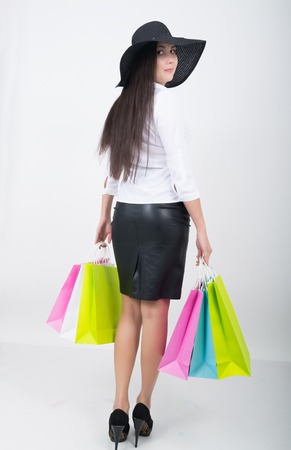 Full length of a beautiful young asian lady in white blouse and black leather skirt holding colorful bags. Girl goes shopping Stock Photo