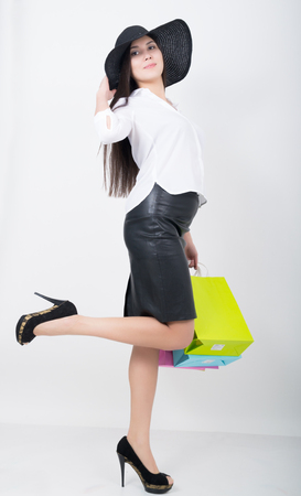 utmost: Full length of a beautiful young asian lady in white blouse and black leather skirt holding colorful bags. Girl goes shopping Stock Photo