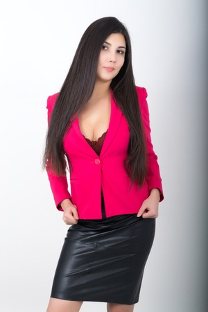 leather skirt: A young pretty slim asian woman in a black leather skirt and a red jacket. Stock Photo