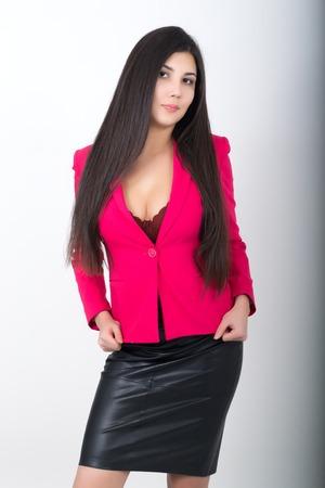 blusa: Una mujer asiática joven bonita delgada en una falda de cuero negro y una chaqueta roja. Foto de archivo
