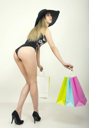 utmost: beautiful young lady in a bathing suit, big black hat on high heels, holding colorful bags. Girl goes shopping.