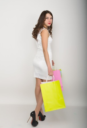 utmost: beautiful young lady in a little white dress on high heels, holding colorful bags. Girl goes shopping.