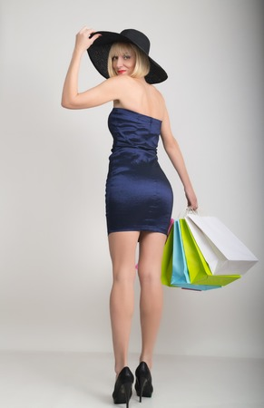 utmost: beautiful young lady in a little blue dress on high heels, holding colorful bags. Girl goes shopping. Stock Photo