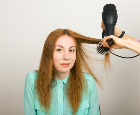 beautiful bangs: Beautiful young red-haired girl at the hairdresser makes blow drying, shorn bangs, hair polishing.