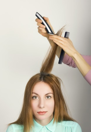 bangs: Beautiful young red-haired girl at the hairdresser makes blow drying, shorn bangs, hair polishing.