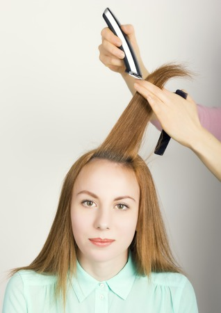 Beautiful young red-haired girl at the hairdresser makes blow drying, shorn bangs, hair polishing.