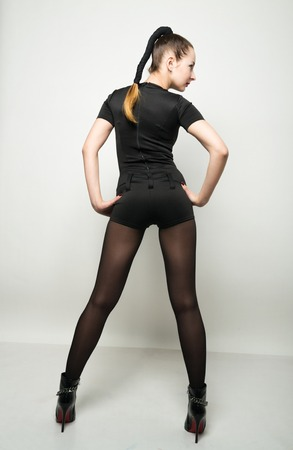 pantsuit: sexy slim young woman  in a black short trouser suit posing in high heels. back view. Stock Photo
