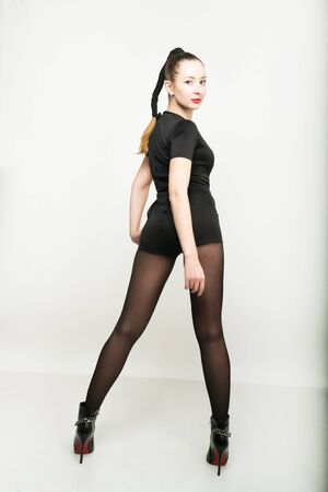centrality: sexy slim young woman  in a black short trouser suit posing in high heels. back view. Stock Photo