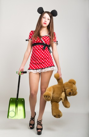 busty: Busty beautiful young girl in a short dress with polka dots, bear in one hand and a shovel in the other teddy bear. Stock Photo