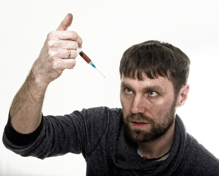 drug use: The social problem - addiction. Young sad man holding syringe to drug use.