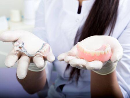 의치를 보유하는 아름 다운 아시아 젊은 여자 치과 의사입니다.