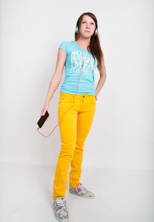 ティーンエイ ジャーのあなたのスマート フォンから音楽を聴いて黄色パンツの女の子。