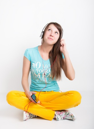 lockdown: teenager girl in yellow pants, listening to music from your smartphone. Stock Photo