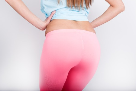 decollete: beautiful slender athletic girl in pink leggings, a blue tank top and colorful Sneakers. nice pop, back view.