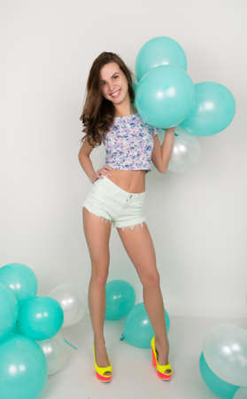 high def: beautiful curly girl in multi-colored top, white shorts and bright shoes playing with balloons.