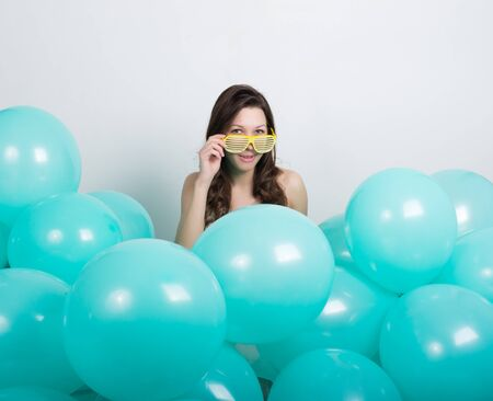 high def: beautiful curly girl in a white dress and sunglasses in the style of disco playing with balloons.