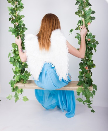 leggy: Beautiful young leggy redhaired woman in a long blue dress on a swing, wooden swing suspended from a rope hemp, rope wrapped vine and ivy. angel wings behind.
